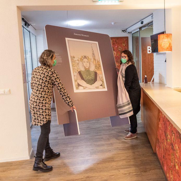 Doortje Hakkennes brengt samen met Museum Plus Bus-medewerkster Elise het Zeeuws Meisje binnen.