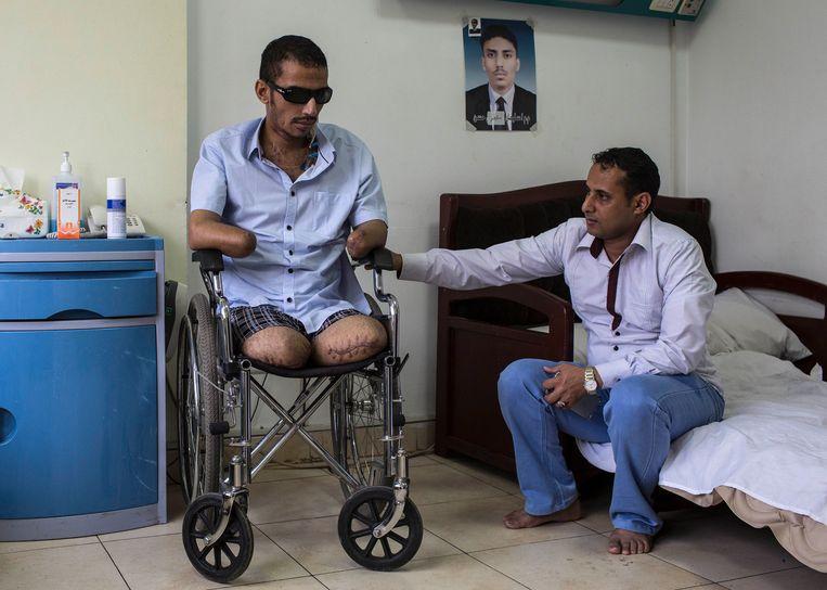 Suleyman Mutahar Hasan verloor zijn benen, armen en het zicht in zijn ogen. Zijn broer houdt hem gezelschap in het ziekenhuis. Aan de muur een foto van Hasan in betere tijden. Beeld Asmaa Waguih
