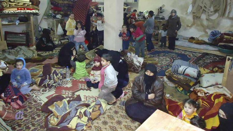 Inwoners van de zwaar gebombardeerde wijk Baba Amro in de stad Homs zoeken bescherming. Beeld reuters