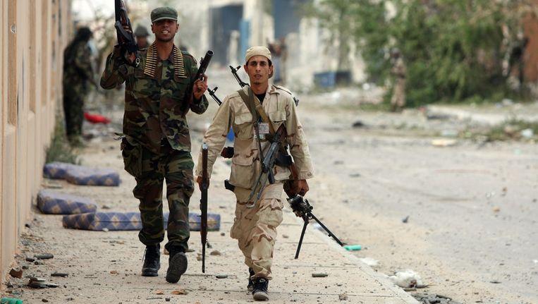 Een rebel draagt het wapen van een Kaddafi-loyalist, gisteren in Sirte. Beeld afp