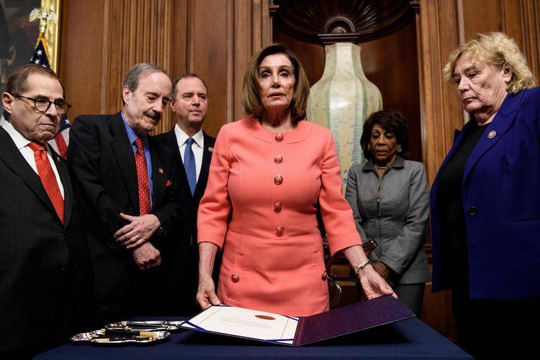 Voorzitter Nancy Pelosi van het Huis van Afgevaardigden ondertekent de aanklachten tegen president Trump. Beeld AFP