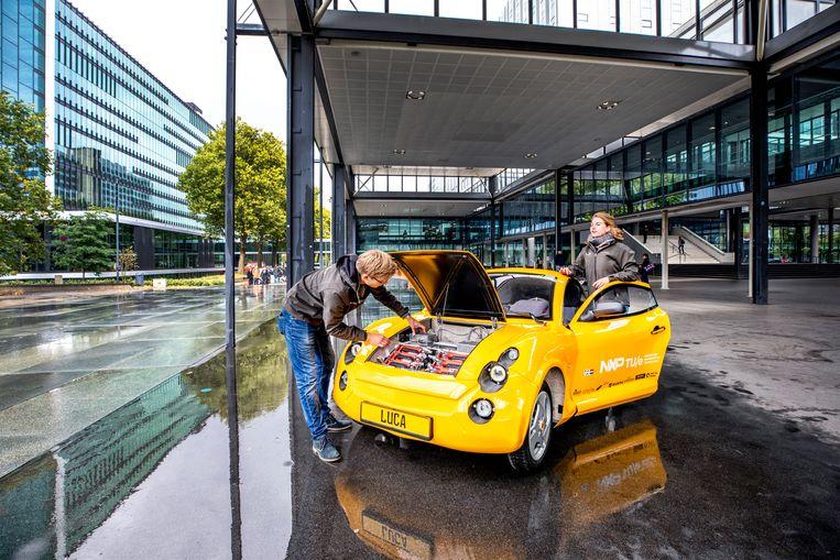 Twee studenten die meewerkten aan de ontwikkeling van de Luca. De auto heeft geen laklaag, maar is bedekt met een zonnebloemgeel folie dat er makkelijk af te halen is. Beeld Raymond Rutting / de Volkskrant