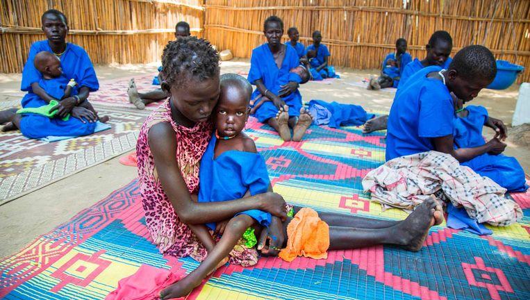 Moeders met hun zwaar ondervoede kinderen begin deze maand in het Zuid-Soedanese Ganyiel Panyijiar. Honderdduizend mensen in Zuid-Soedan dreigen van de honger om te komen. Beeld AFP