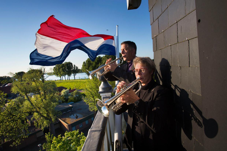 Trompettist Arjan Muller en zijn partner Ineke van Kapel spelen vanaf de dorpskerk in Puttershoek het trompetsignaal Taptoe. Beeld Arie Kievit