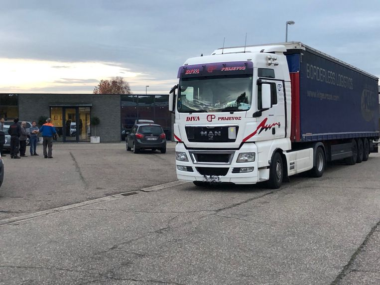 De bewuste vrachtwagen met de chauffeur met blauwe jas met oranje schouderstukken (links in beeld)