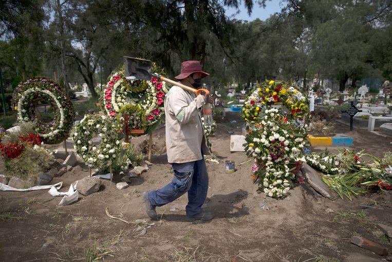 Een grafdelver op het deel van het kerkhof San Lorenzo Tezonco Iztapalapa in Mexico-Stad waar slachtoffers van het coronavirus worden begraven. Beeld AP