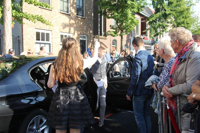 De kinderen worden geheel in stijl verwelkomd nabij de rode loper, en de toeschouwers kijken toe