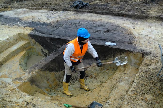 Archeoloog Hendrik Uleners graaft de donker gekleurde waterput bloot