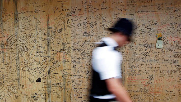 Een Britse politieagent loopt langs een muur vol met protestberichten van Zuid-Londense inwoners aangaande geweld in de buurt, 2011. Beeld ANP
