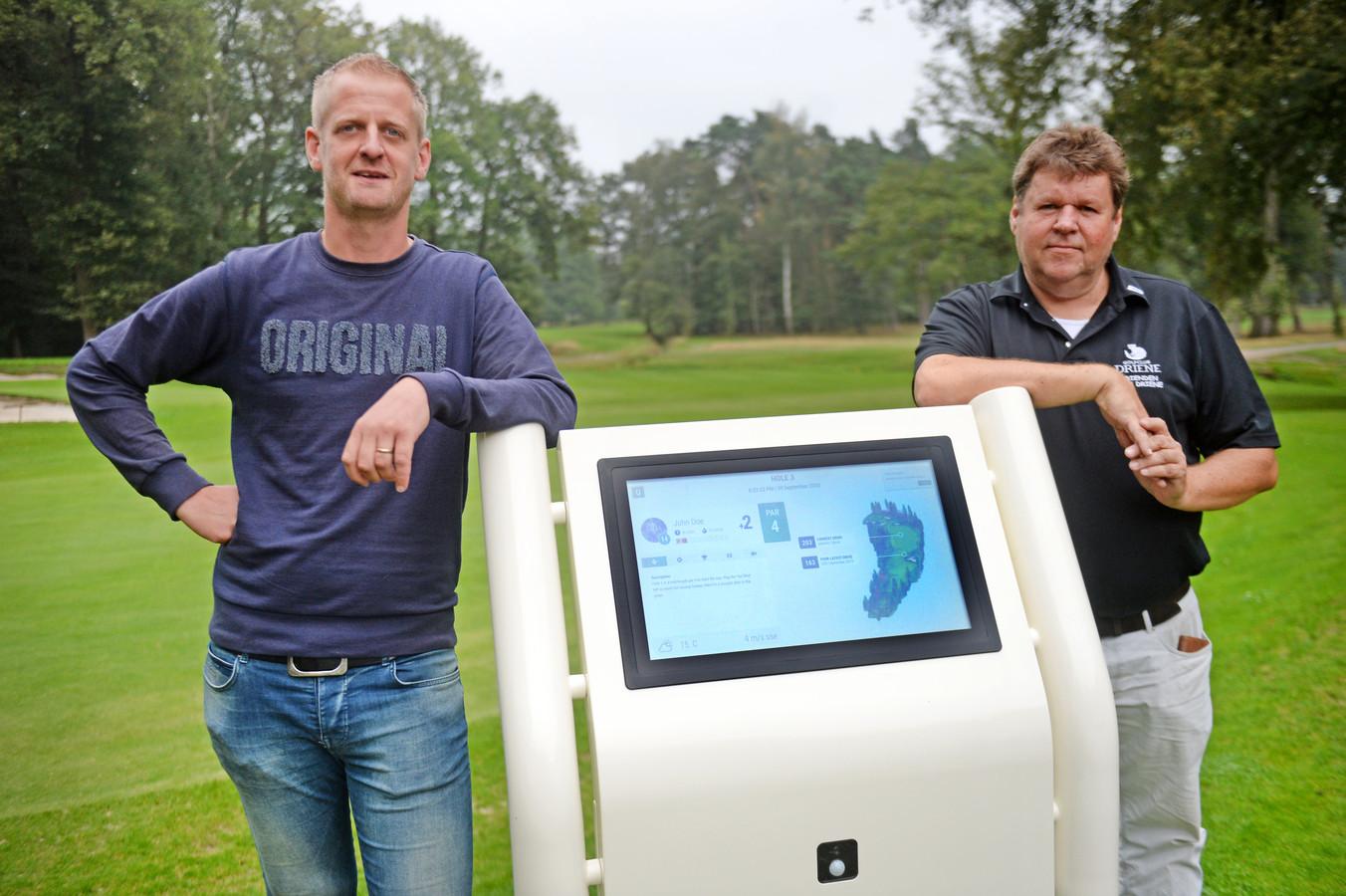 Ontwerper Jaro Tijhuis (links) en bestuurslid Ton de Vent bij de nieuwste digitale display. Golfclub Driene dient als pilot project voor het systeem van Tijhuis.