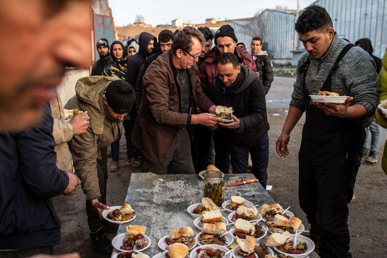 Een Bosnische vrijwilliger deelt voedsel uit aan Algerijnse migranten. Beeld Getty Images
