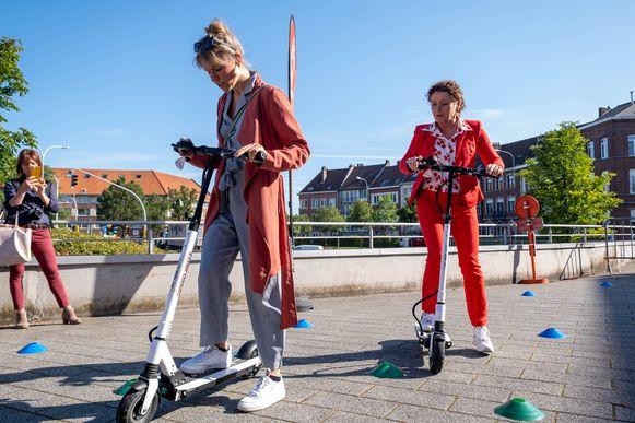 De e-stepgebruikers testen hun vaardigheden op het parcours. Rechts zien we minister van Mobiliteit Lydia Peeters
