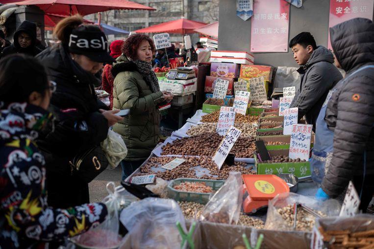 Mensen kopen noten bij een marktkraam in Beijing.   Beeld AFP
