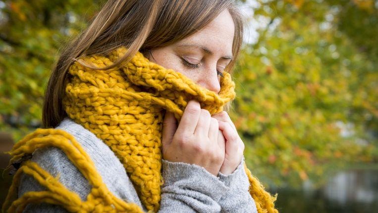 Een vrouw kruipt weg in een dikke sjaal. Beeld anp