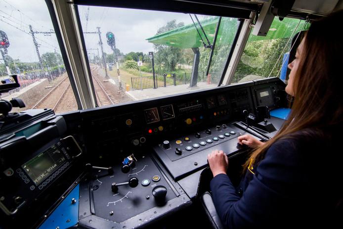 Een medewerker van de NS aan het werk in de cabine van een trein. Nu stuurt ze nog helemaal zelf, maar dat kan in de toekomst gaan veranderen.