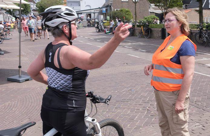 Corona-coach Laurence Haack beantwoordt vragen van een fietser. In de Ooststraat mocht niet worden gefietst.