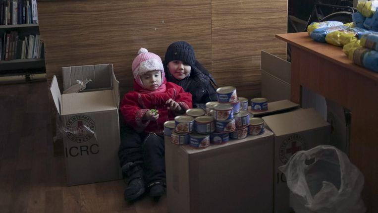 Kinderen zitten naast wat humanitaire hulp in het Paleis van Cultuur, dat voor de gelegenheid omgetoverd werd tot schuiloord.