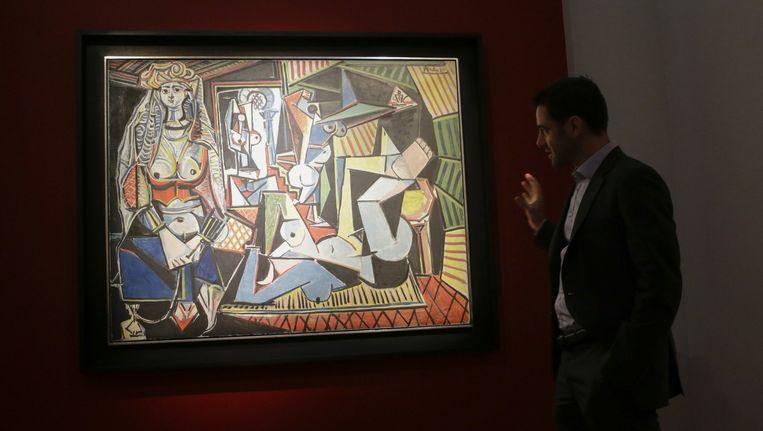 Een medewerker van Christie's staat bij 'Les Femmes d'Alger' van Picasso. Beeld afp