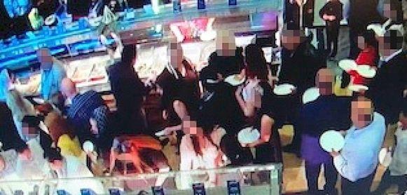 Beelden van de bewakingscamera tonen de chaos die ontstond toen een grote groep het buffet bestormde.