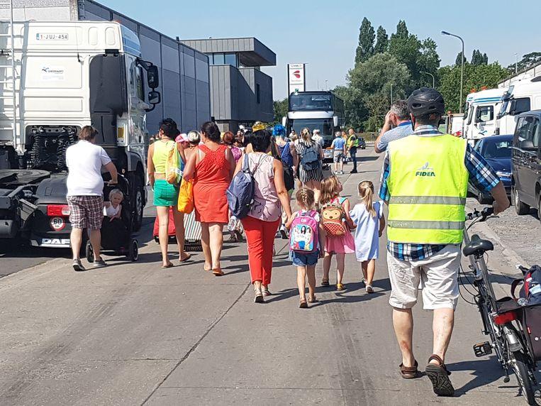 De reizigers wandelen richting de ingelegde bussen.