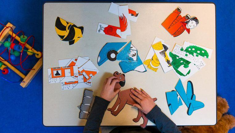 Een meisje maakt een puzzel in de speelkamer van een jeugdhulpcentrum. Beeld anp
