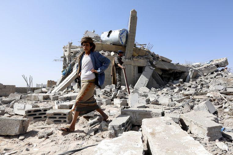 Een man loopt over een ingestort gebouw dat door een luchtaanval werd geraakt in de noordelijke buitenwijken van hoofdstad Sanaa.