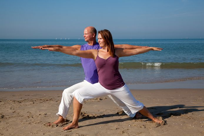 Carla tijdens een yogales op het strand.