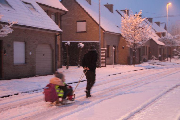 Een papa trekt zijn kindje met de slee naar school.