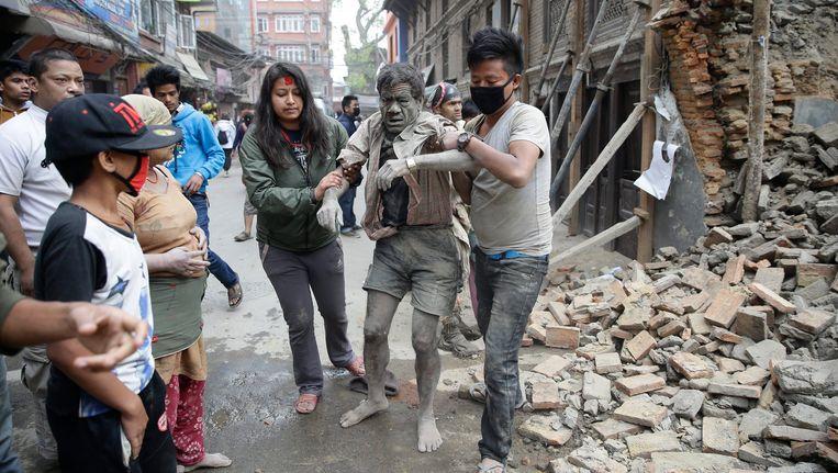 Een slachtoffer wordt in Kathmandu onder het puin van een ingestort gebouw vandaan gehaald. Beeld epa
