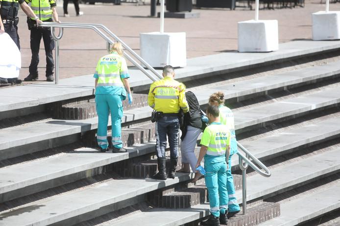 Aan de hand van ambulancepersoneel en een agent liep de vrouw de trap op richting de ambulance.