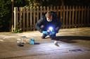 Een technisch rechercheur doet onderzoek in de Zwolse straat de Alm, nadat eerder op de avond een molotovcocktail tegen een woning is gegooid.