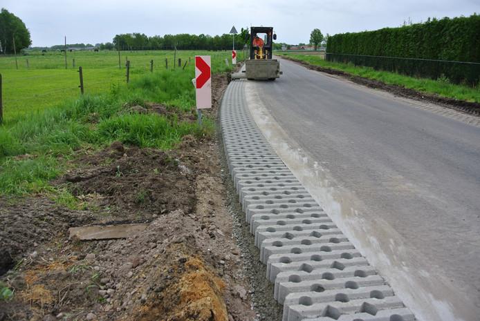 Wegenbouwers maken tegenwoordig eerst een goede, stabiele fundering van gebroken puin. Daarna komen de graskeien langs het asfalt.