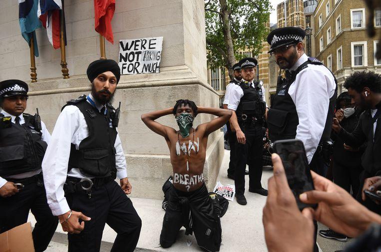 Een demonstrant knielt tijdens de betoging in Londen. Beeld EPA