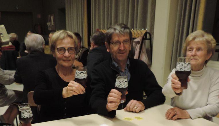Vrijwilligers Christiane Vanhalst, Luc Desmet en Noëlla Devolder toasten met het Sint-Crispijnbier.