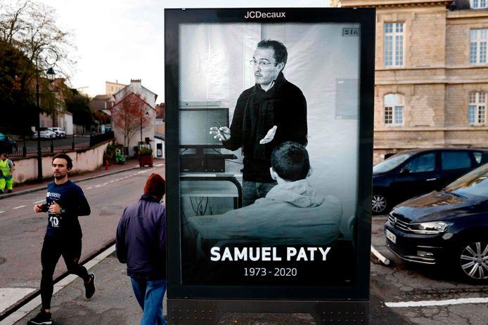 Voetgangers passeren een poster met daarop de vermoorde Franse leraar Samuel Paty.