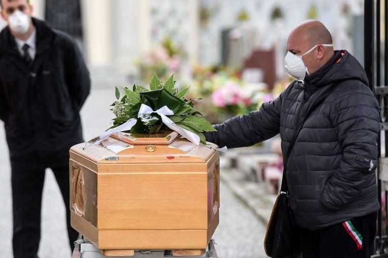 Een man neemt afscheid van zijn bezweken familielid tijdens een begrafenis in Bolgare, Lombardije.