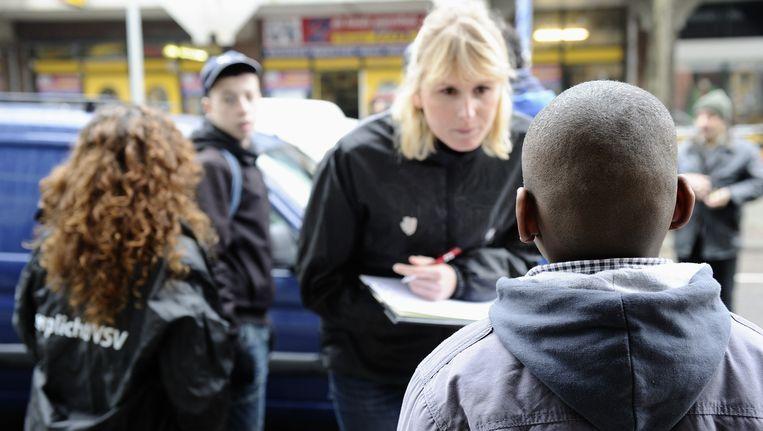 Leerplichtambtenaren controleren woensdag samen met politieagenten in de Schilderswijk in Den Haag. Zij spreken kinderen aan en vragen hen waarom ze niet op school zijn en controleren hun verhaal. Beeld ANP XTRA