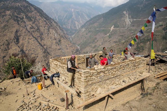 Bouwvakkers in Nepal werken aan de wederopbouw van een woning na de verwoestende aardbeving die het land in 2015 trof.