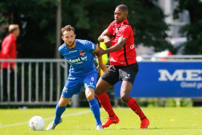 De Treffers-middenvelder Robin Janssen (l) houdt AFC'er Melvin Grootfaam van zich af.