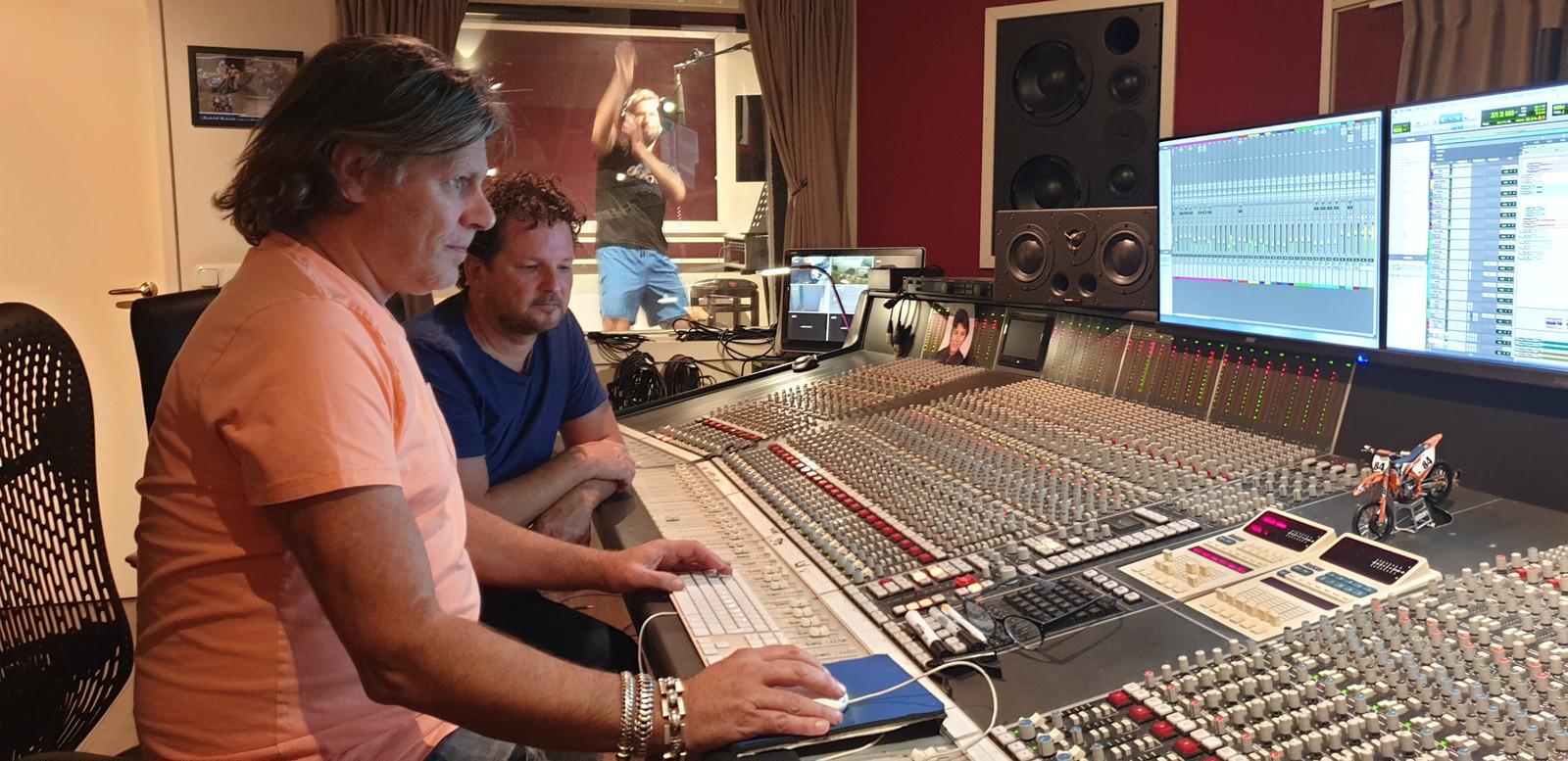 Producer Edwin van Hoevelaak (links) en bandlid Ronald ten Bos zijn bezig met de eerste singles die de band over enkele maanden hoopt uit te brengen. Zanger Eric ten Bos zingt zijn partijen in op de achtergrond.