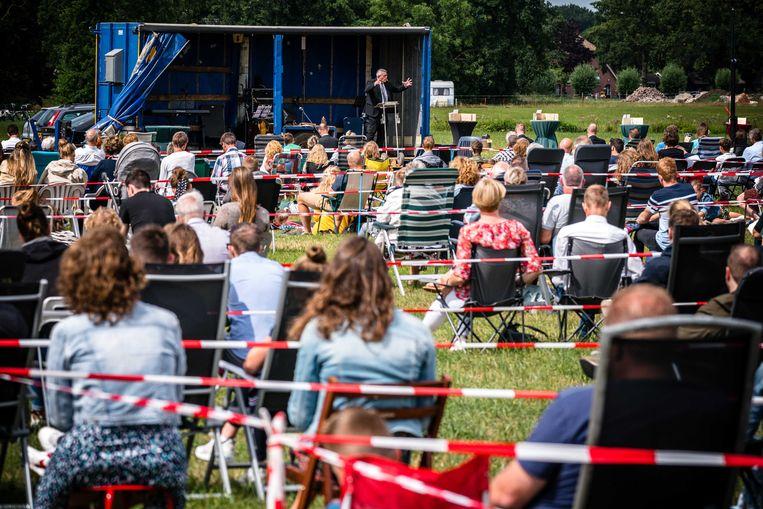Gelovigen in Barneveld tijdens een dit weekend in een weiland gehouden 'kerkdienst'.  Tijdens de openluchtdienst van de Hervormde Gemeente Barneveld mocht uit volle borst worden meegezongen.  Beeld ANP