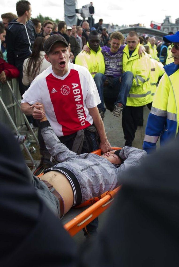 Een man wordt afgevoerd op een brancard op het Museumplein. Foto Beeld anp