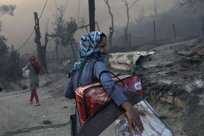 Een vrouw verzamelt haar schamele bezittingen, nadat de brand haar onderkomen in de as legde.