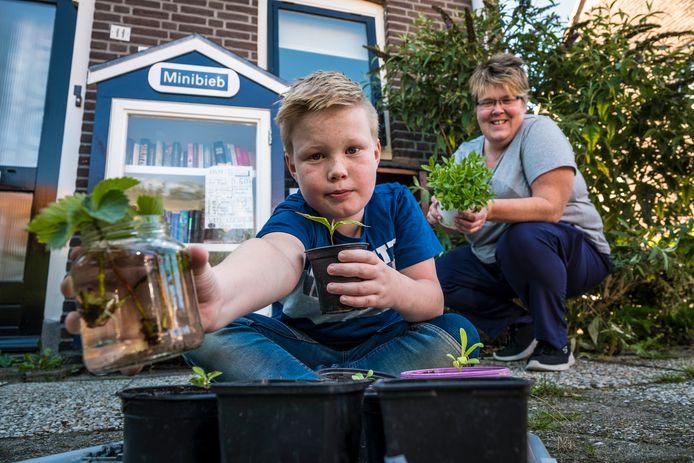 Inge Docter krijgt hulp van haar zoon Finn (9) bij het stekken van aardbeienplantjes en het aanvullen van de Stekjesbieb.