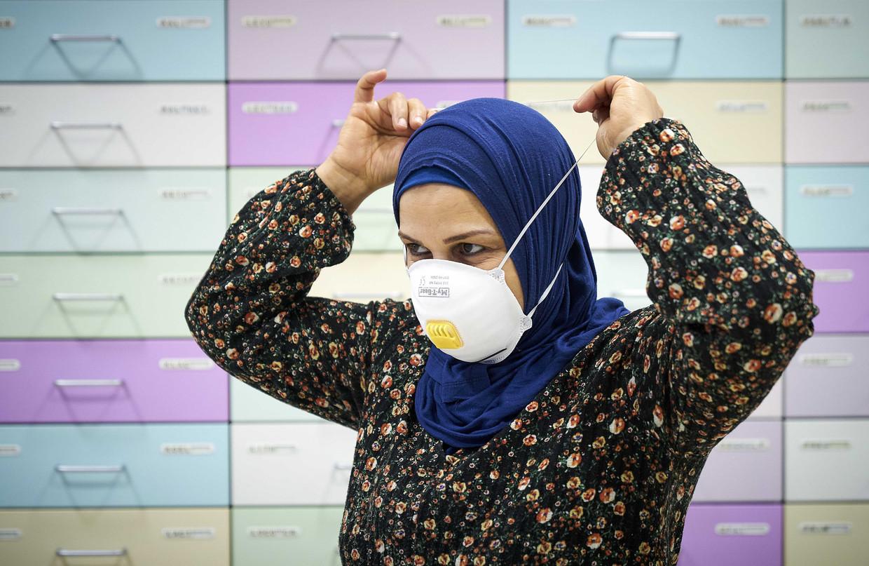 Een werknemer van de apotheek demonstreert een mondkapje.