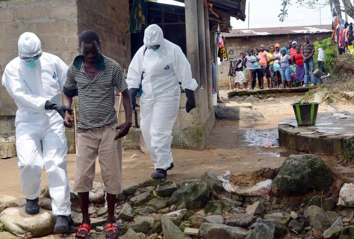Hulpverleners begeleiden een met ebola besmette man naar een ziekenhuis in Monrovia in Liberia.