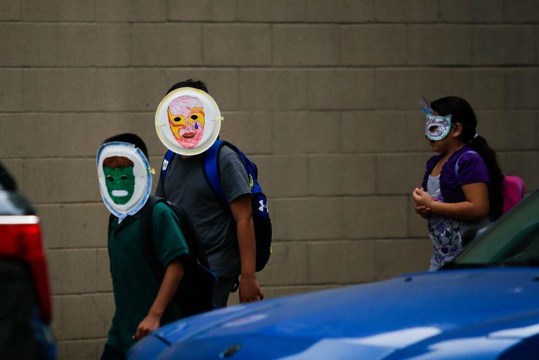 Kinderen van migranten, die zijn gescheiden van hun ouders, bij een opvang in New York. Ze hebben zelf maskers gemaakt in de opvang. Beeld Corbis via Getty Images