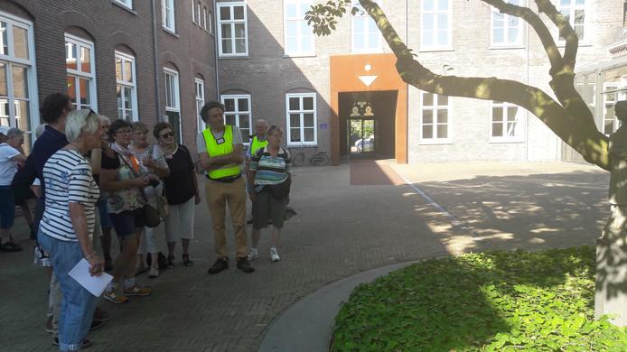 Deelnemers aan de Brabantse Heemdagen bekijken het beeld van Cecilia, de naamgeefster van het klooster in Zijtaart.