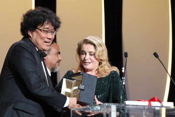 """De Zuid-Koreaanse filmregisseur Bong Joon-Ho (L) ontvangt de Gouden Palm voor zijn film """"Parasite"""" uit handen van de Franse actrice Catherine Deneuve."""