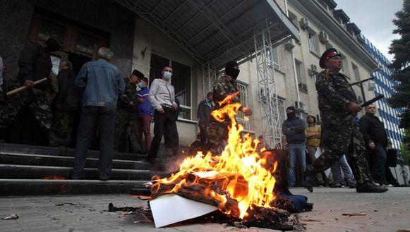 Pro-Russische activisten verbranden Oekraïense symbolen voor het politiecommissariaat in Loehansk.